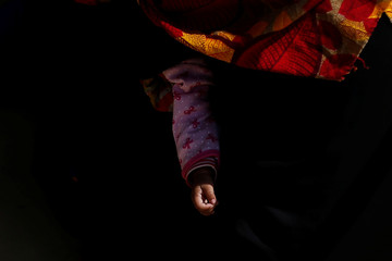 Rohingya refugee holds her baby as she waits for a food distribution at the Balukhali refugee camp near Cox's Bazar