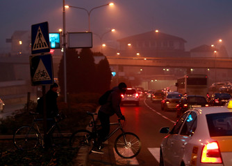 Vehicle traffic and cyclists are seen during evening fog and air pollution covering Skopje