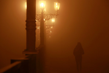 Person walks during evening fog and air pollution covering Skopje
