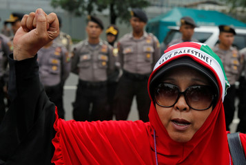 A Muslim woman shouts slogans during a protest to condemn Washington's decision to recognize Jerusalem as Israel's capital, outside the U.S. embassy in Jakarta
