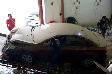 Employees work on a new arrival of cars at the workshop of El Faqyier (The Poor), a crash-damaged vehicles and second-hand car shop, in Cairo