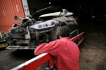 An employee works on a new arrival of cars at the workshop of El Faqyier (The Poor), a crash-damaged vehicles and second-hand car shop in Cairo