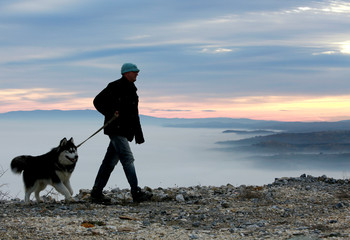 Man walks his dog as fog blankets Skopje