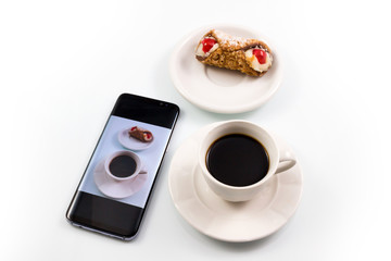 Picture coffee and sweet cookie with a smartphone in white background.
