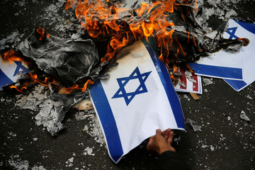 A participant burns an Israeli flag mockup during a protest to condemn Washington's decision to recognize Jerusalem as Israel's capital, outside the U.S. embassy in Jakarta
