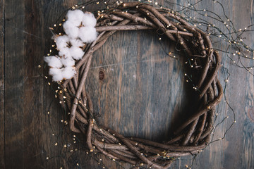 Beautiful hand-made wooden festive wreath with cotton flowers and fireflies garland around it on the old rustic wooden table background, top view