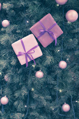 Toned photo of Christmas tree with balls, purple boxes