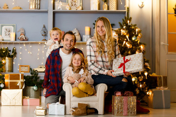 New Year's picture of happy family on background of Christmas decorations, pine