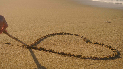 Painted hart on brown sand, washed off by wave, sunset, sea background. Concept: rest, love, style life, sea, beach, coast.