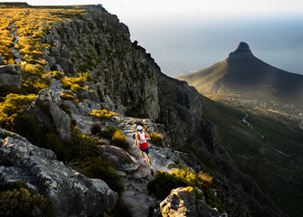 Trail runner running along a trail on the top of Table Mountain in Cape Town while out training in the mountains at sunset