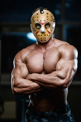 horror brutal mask man strong bodybuilder athletic fitness man in scary hockey mask in the gym
