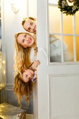 Photo of happy family with daughter peeking out from behind door with Christmas wreath