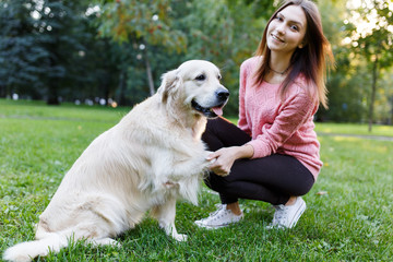 Image of woman with dog giving paw on lawn in summer park
