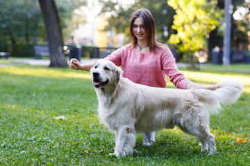 Photo of brunette with dog on agreen lawn