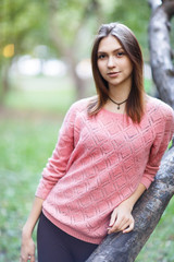 Image of young woman in pink blouse walking