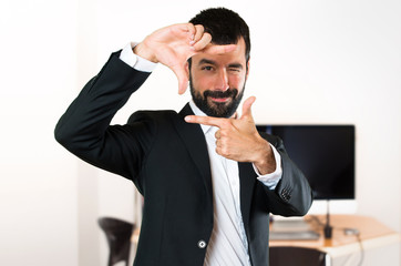 Handsome businessman focusing with his fingers in the office