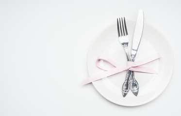composition for Valentine's day knife and fork tied with ribbon on a plate with decorative hearts