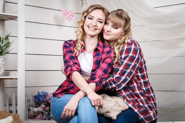 Two blond sisters in the room with white walls