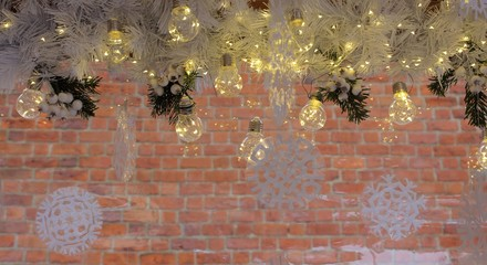 Merry Christmas and Happy New Year festive shiny decoration. White pine needles and snowflakes and lighting lamps against unfocused brick background. Winter holidays decoration background.