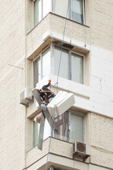 Wall Thermal insulation, industrial climbing, high-altitude work, insulation of walls with foam plastic or Styrofoam