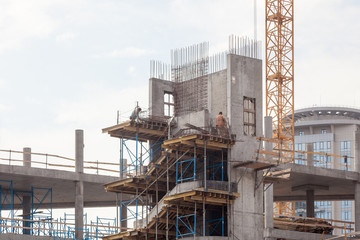 Residental building under construction. Precast concrete stairs installed. Walls made of aerated concrete blocks. Crane and new mutlistoty building construction site. Construction of staircases.