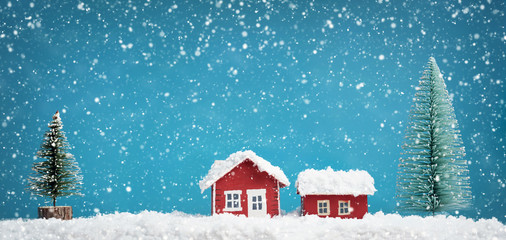 Small red house model covered with snow in winter