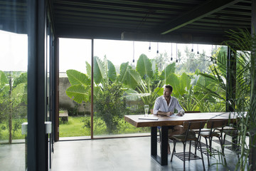 Mature man sitting at table in front of lush garden, writing