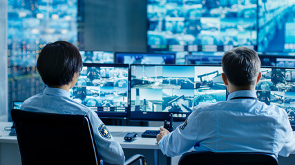In the Security Control Room Two Officers Monitoring Multiple Screens for Suspicious Activities, They Report any Unauthorised Activities. They Guard Object of National Importance. Wall mural