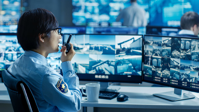 In the Security Control Room Officer Monitors Multiple Screens for Suspicious Activities, He Reports any Unauthorised Activities in His Walkie-Talkie. He's Surrounded by Monitors.