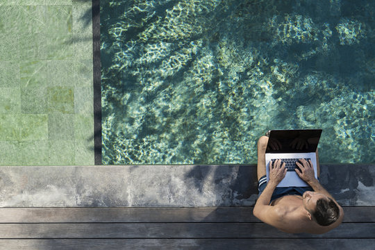 Mature man sitting at the poolside, using laptop
