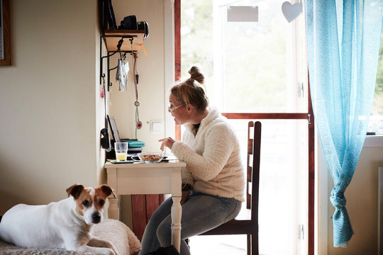 Disabled young woman using laptop at desk with dog in foreground at home