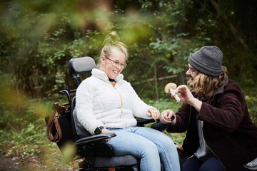 Male caretaker showing mushroom to disabled woman in wheelchair at forest