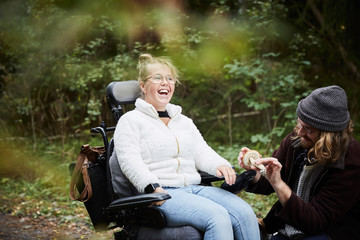 Cheerful disabled woman in wheelchair by caretaker holding mushroom at forest