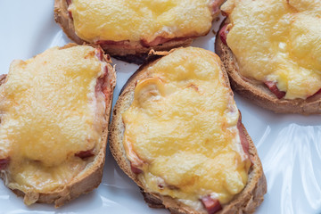close-up of baked hot sandwiches with cheese and sausage on white plate