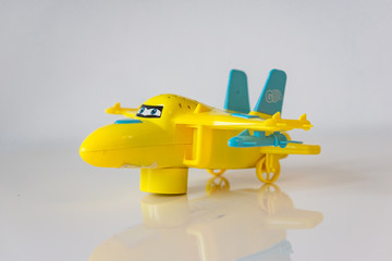 Closeup of yellow plastic toy airplane on a white table.