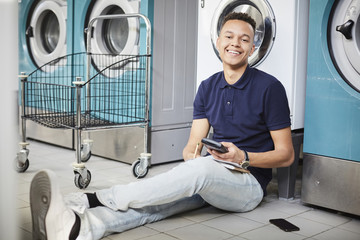 Portrait of smiling man holding calculator and studying while sitting besides washing machine
