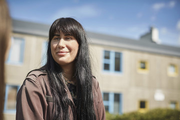 Smiling young woman with long black hair at university campus