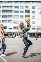 Full length side view of friends playing basketball against building