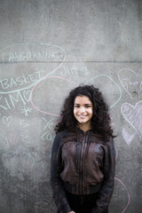 Portrait of smiling teenage girl standing against chalk drawing on gray wall in city