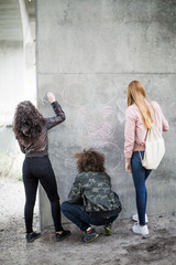 Friends drawing on concrete wall with chalk