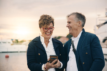 Happy senior woman using smart phone while standing by man at harbor
