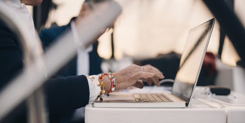 Cropped image of senior woman using laptop with senior man in background at yacht