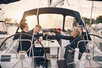 Senior woman passing battery charger to female friend while traveling in yacht