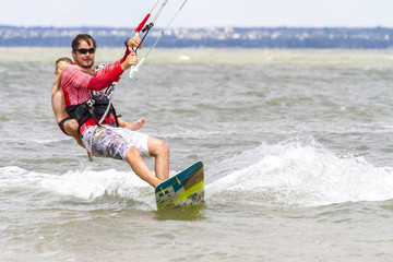 Dad and son are kitesurfing on the sea. The son clings to Papa's back