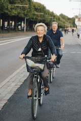 Smiling senior woman with man riding bicycles on city street