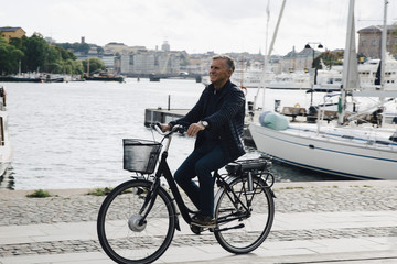 Full length of senior man riding bicycle on road by harbor