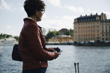 Side view of senior woman holding mobile phone while standing by sea in city
