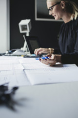 Female engineer holding pen while using calculator on desk at home office