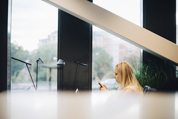 Side view of young blond businesswoman using smart phone at office