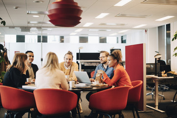Multi-ethnic business colleagues sitting at conference table in office during meeting